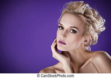 The image of a beautiful luxurious woman on purple background. Studio shot