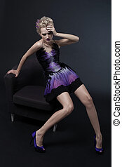 The image of a beautiful luxurious woman sitting on chair. Studio shot