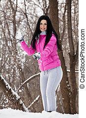 girl plays at snowballs
