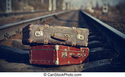 The image of vintage suitcases forgotten on railway tracks.