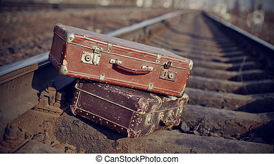The image of vintage suitcases thrown on railway tracks.