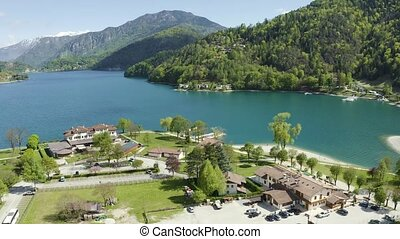 The Improbable aerial landscape of village Molveno, Italy, azure water of lake, empty beach, snow covered mountains Dolomites on background, roof top of chalet, sunny weather, a piers, coastline