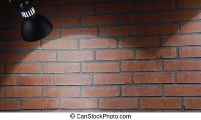 The incandescent lamp shines on a brick wall, the texture of a brick.