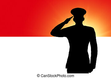 The Indonesian flag and the silhouette of a soldier's...