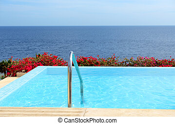 The infinity sea view swimming pool with jacuzzi at luxury...