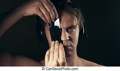 The insane person in the headphones glues his eyes with...