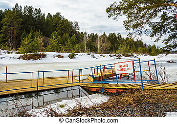 """The inscription """"bathing is forbidden"""" on the pontoon on the shore of the frozen"""
