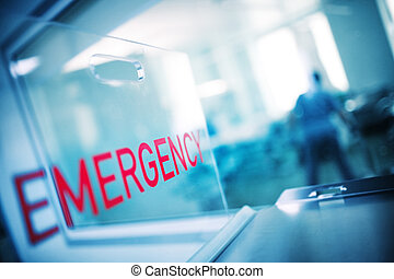 """The inscription """"emergency"""" on the plastic glass against the background of the hospital emergency room"""