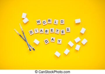 The inscription from wooden blocks world diabetic day and cubes of pressed sugar and insulin syringes on a yellow background.