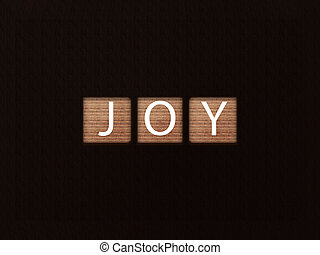 The inscription JOY on wooden blocks on black background. Letter on wooden cube.