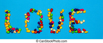 the inscription love, lined with colored colored stones. spring mood. banner