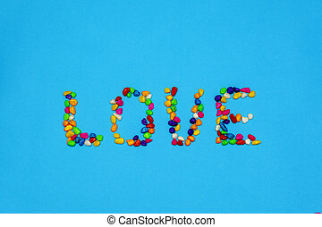 the inscription love, lined with colored colored stones. spring mood