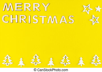 The Inscription Merry Christmas made of wooden letters, lying flat from above, isolated on a yellow, rough background. White wooden Christmas trees arranged in a row at the bottom.