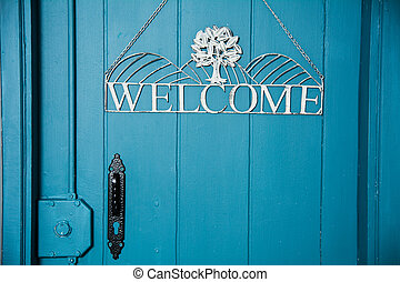 The inscription on the blue door welcome. Invitation to...