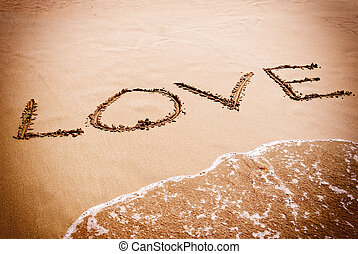 The inscription on the sand near the sea and the waves - LOVE. Background for Valentines Day.
