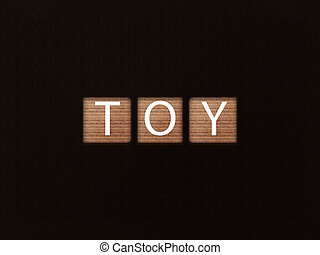 The inscription TOY on wooden blocks on black background. Letter on wooden cube.