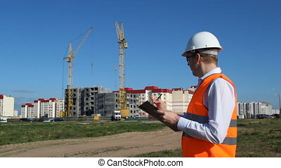 the inspector in black glasses conducts an inspection of the construction of a residential house, marks a tablet
