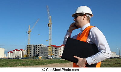 the inspector in black glasses is holding a laptop and talking on the phone on the background of the construction of a residential house