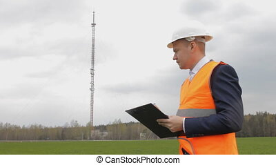 the inspector makes notes on the television tower, antenna