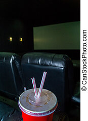 The interior of a cinema hall with black leather seats and a white screen. The film does not show and no people.