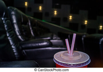 The interior of a cinema hall with black leather seats. The film does not show and no people.