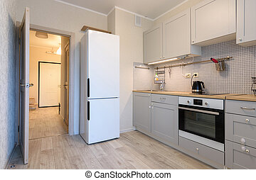 The interior of a small cozy kitchen in the apartment, the interior door to the kitchen is open