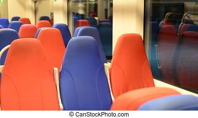 interior of an empty train with red and blue seats