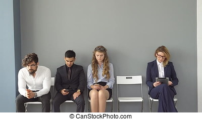 The interview for the job. Recruits are bored and enjoy the gadgets. Young people expect interviews sitting on chairs in an office building.