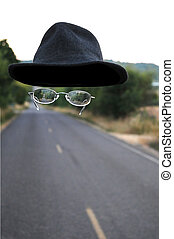 An invisible man walking down the road wearing only a hat and a pair of glasses.