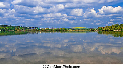 The island among the lake on which grow tall green trees against a blue sky with clouds