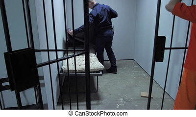 The jailer examines the prison cell