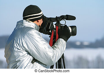 The journalist with a videocamera in the winter morning