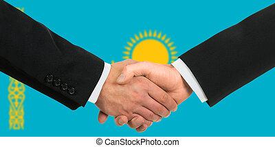 The Kazakh flag and business handshake