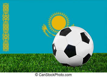 The Kazakh flag and soccer ball on the green grass.
