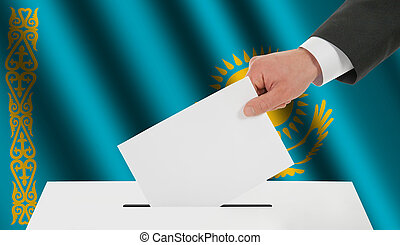 The Kazakh flag and the hand with the bulletin about the ballot box