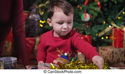 The kid at the Christmas tree. Interested baby playing with...