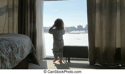 The kid, child knocks on the window. Girl looking out the window. Slow motion