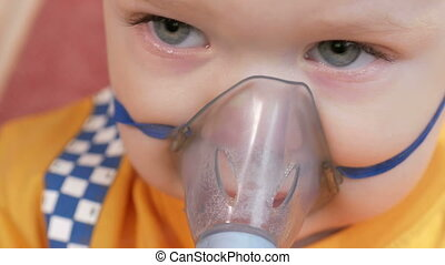 The kid himself holding a mask from an inhaler and breathes ...