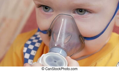 The kid himself holding a mask from an inhaler and breathes the medicine at home. Treats inflammation of the airways via nebulizer. Preventing asthma and cough.