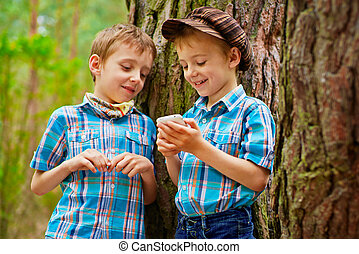 The kid is showing his brother different games on mobile phone