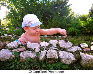 The kid is watching a snail