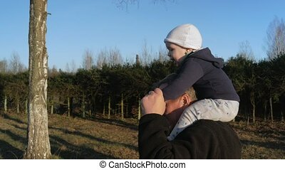 The kid sits on his grandfather's neck and they walk in the park at sunset. My granddaughter likes to ride a man.