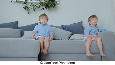 The kids are watching tv. Small children sitting on the...