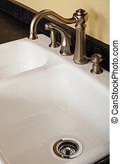 Close-up of a brushed nickle faucet with a strem of water flowing through it.