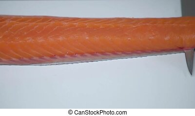 The knife cuts the fillets of red salmon fish.
