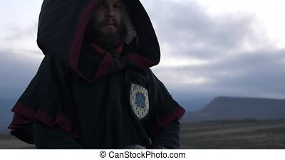 The knight looks arrogantly His head covered by hood Wind...