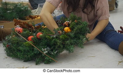 The lady designer decorates the Cristmas wreath sitting on...
