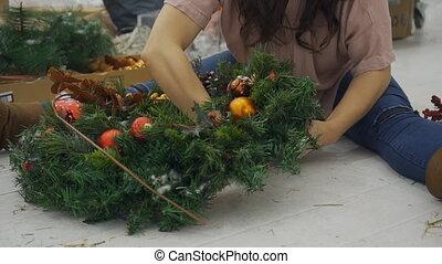 The lady designer decorates the Cristmas wreath sitting on...