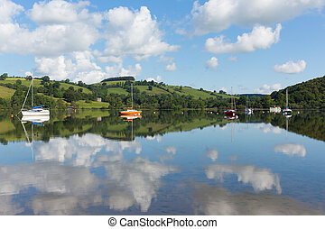 The Lake District popular beautiful UK tourist destination Ullswater Cumbria North England in summer with boats blue sky and cloud reflections