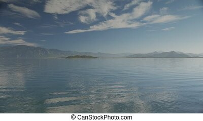 The lake view with small waves and islands, hills and cloudy sky on the background. 4k